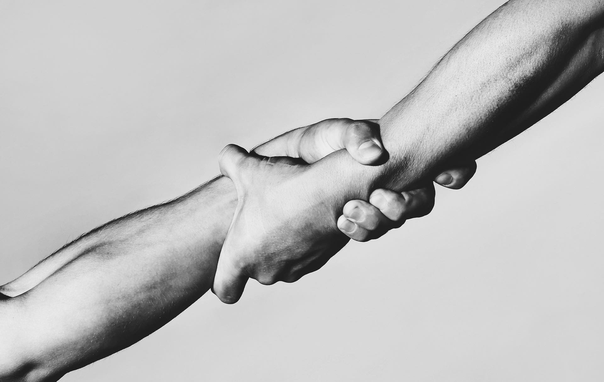 Two hands, helping hand of a friend. Handshake, arms, friendship. Friendly handshake, friends greeting, teamwork, friendship. Rescue, helping gesture or hands. Strong hold. Close-up. Black and white